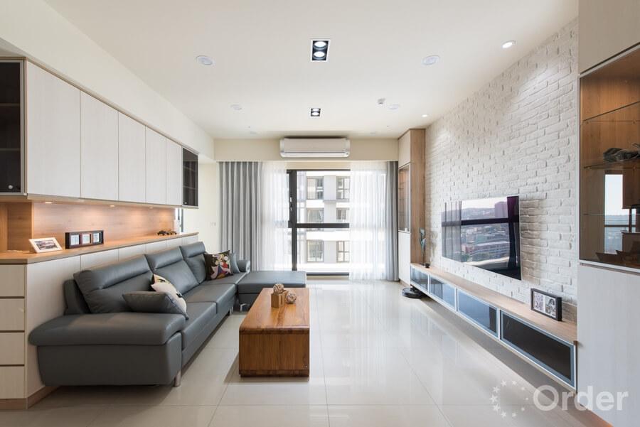 免費設計客廳裝潢整面落地窗帶來自然光線,文化石電視牆搭配優渥實木木紋茶几以及歐德波昂沙發打造舒適宜人客廳場域。