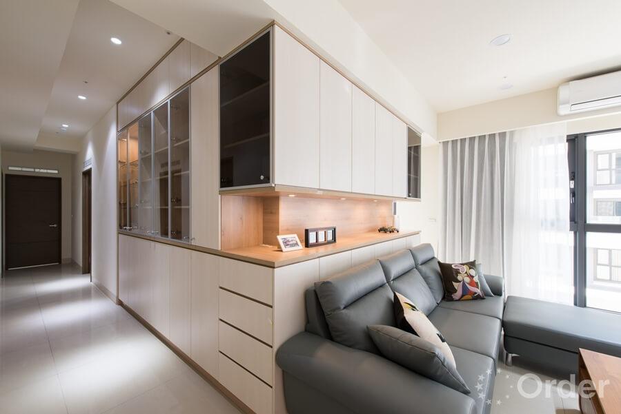 客廳裝潢玻璃窗展示及隱藏拉門等不同風格系統櫃增添了空間的層次,中段木紋展示則暖化了櫃體的線條。