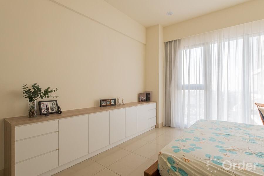 歐德家具利用自然淺色木紋系統板材打造床尾收納櫃,塑造簡約又充滿溫煦感臥室空間。